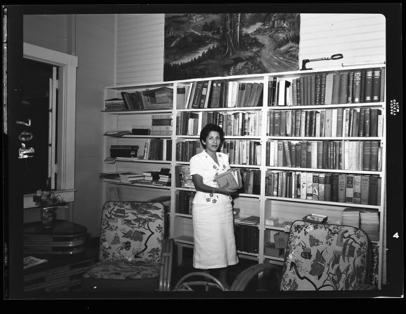 Adela Gómez stands holding a book in front of a bookshelf in James Zetek's office.