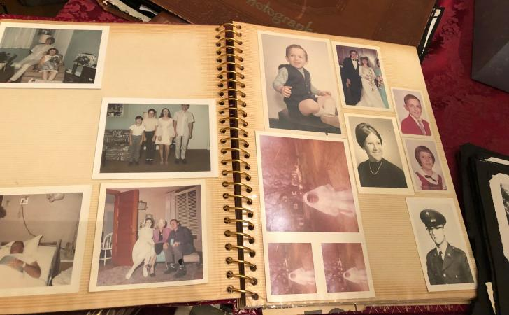 A family photograph album from the mid-20th century open to two pages. An assortment of photographs,