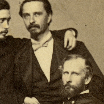 beige carte-de-visite with 4 men posed close together, two seated, with signatures on the bottom