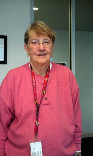 Color portrait of Zoe Martindale standing, wearing a pink shirt and lanyard around her neck with a I