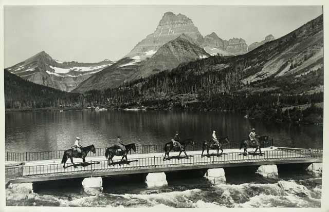 Crossing the New Swift Current bridge on horseback, near the Swift Current waterfalls in Montana's G