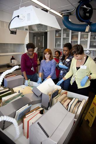 5 women examining archival boxes