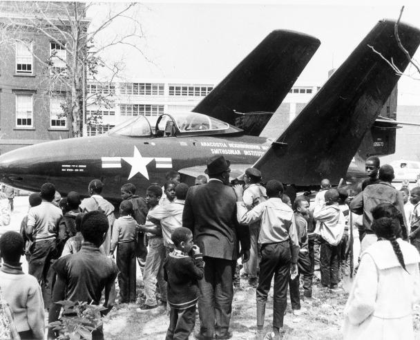 Black and white photograph of airplane with crowd around it.
