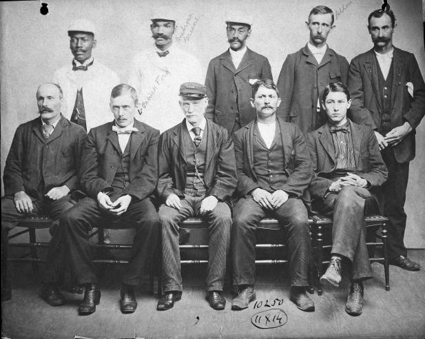 Black and white photograph of group of seated men.