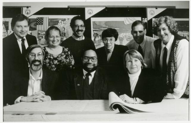 Black and white portrait of group seated behind a table.