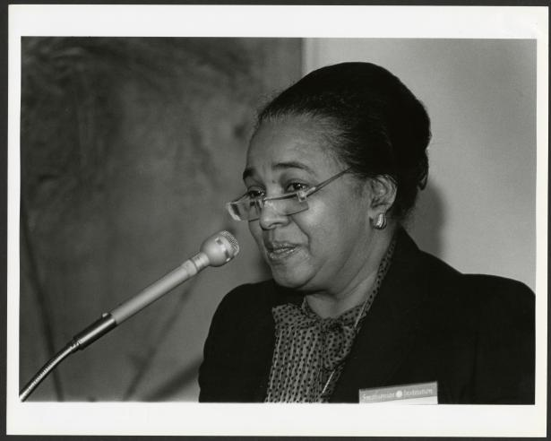 Black and white photograph of woman speaking at microphone.