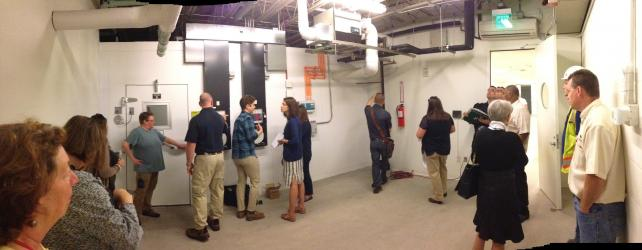 Group of people in white room showing control & monitoring equipment