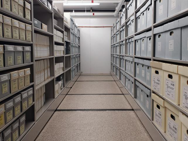 An aisle of metal shelves with archival boxes