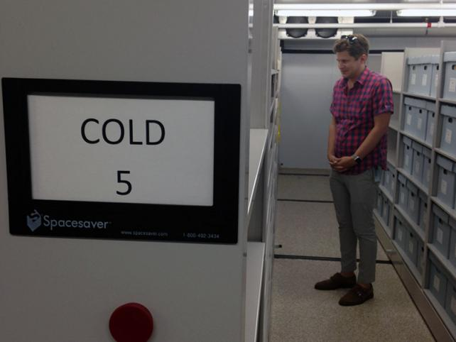 Man standing in row of archival boxes