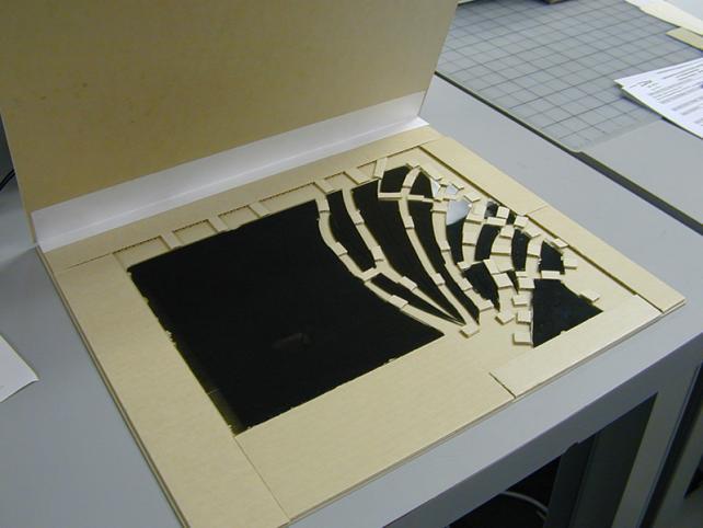 grey folder holding glass negative with buffers between broken pieces