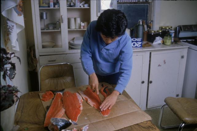 Unidentified woman, a resident of the village of Angoon, preparing sockeye salmon in the traditional