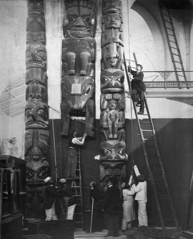 Curators look on as three totem poles are installed in the Northwest Range near the Rotunda of the United States National Museum, now the Arts and Industries Building, by several laborers. Record Unit 95, Smithsonian Institution Archives, Neg. no. MNH-5792.