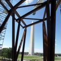 The Washington Monument is seen through installed metal posts.