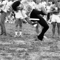 Black and white image of a man jumping in the air doing a Frisbee trick