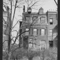 Black-and-white image of a four story townhouse, metal fence, bushes, trees and bicycle appear in front of the townhouse.
