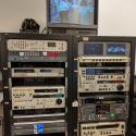 A rack of assorted legacy video decks. A monitor sitting on top of the rack shows a screenshot of a video of a parade in the street.