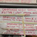 """Long, thin cardboard boxes labeled """"Smithsonian World"""" with various episode titles. The boxes are stacked on one another."""