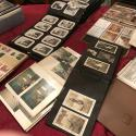 An assortment of common family archival materials laid out on a table with red tablecloth. Various photograph albums and scrapbooks of different ages are open, along with displayed paper documents. A box of vertically stacked photographs is open and displayed off to the side.
