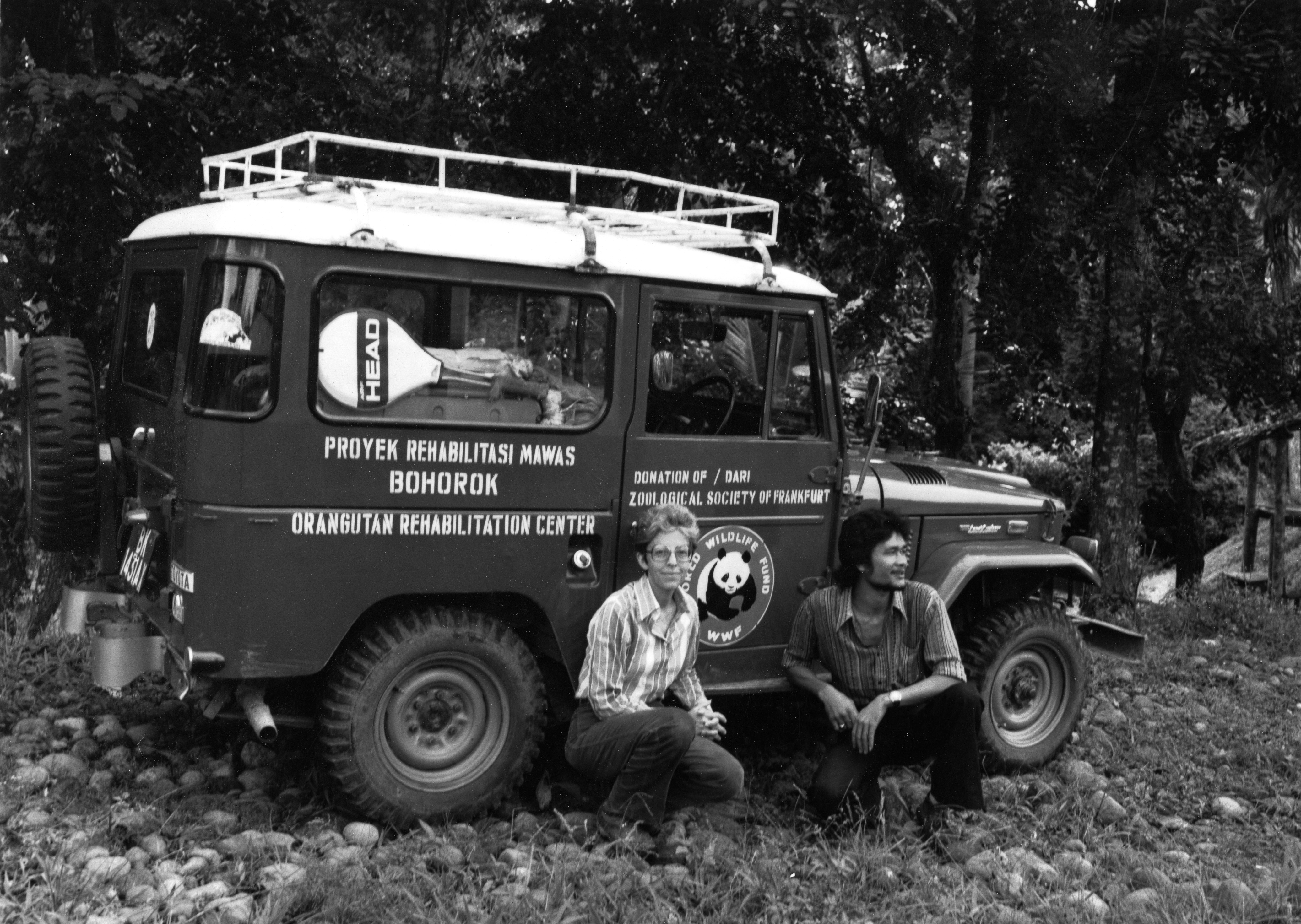 Black and white image of Olga Linares and colleague sitting in front of a field research jeep.